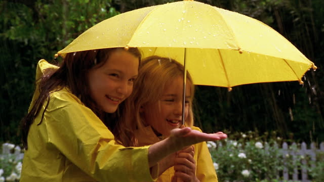 two young girls wearing yellow raincoats and holding a yellow umbrella stick their tongues and hands out in the rain. - yellow stock videos & royalty-free footage