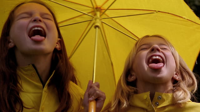 Two young girls wearing yellow raincoats and holding a yellow umbrella stick their tongues out in the rain.
