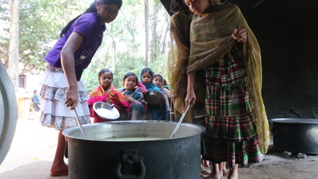 MS of two young girls who are serving food out of a big cooking pot to school children who are standing in line with silver plates in their hands...