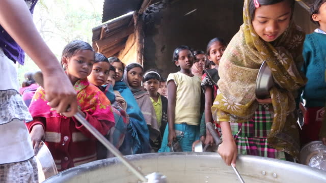 CU of two young girls who are serving food out of a big cooking pot to school children who are standing in line with silver plates in their hands...