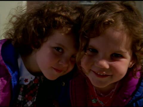 vídeos y material grabado en eventos de stock de two young girls with curly hair peer at camera and smile, usa - usa