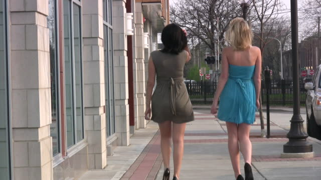 Two young girls women walking. Sexy short dresses. Shopping.