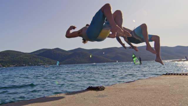 SLO MO zwei junge Burschen, die Durchführung eines zurück Salto ins Wasser