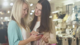 Two young happy girls are using a smartphone in a department store.