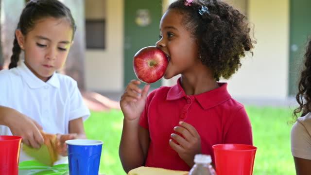 vídeos de stock e filmes b-roll de two young hispanic girls having fun messing around at lunch - merenda escolar