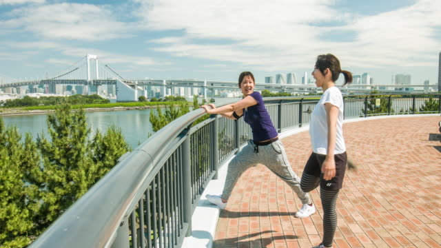 Two young Japanese women stretching outdoor