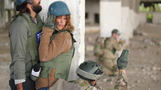 zwei junge journalisten, die sich im kriegsgebiet verstecken - war stock-videos und b-roll-filmmaterial