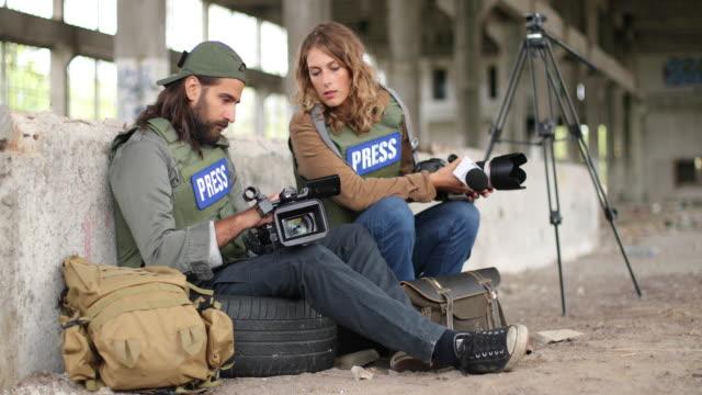 two young journalists in war zone - zaino da montagna video stock e b–roll