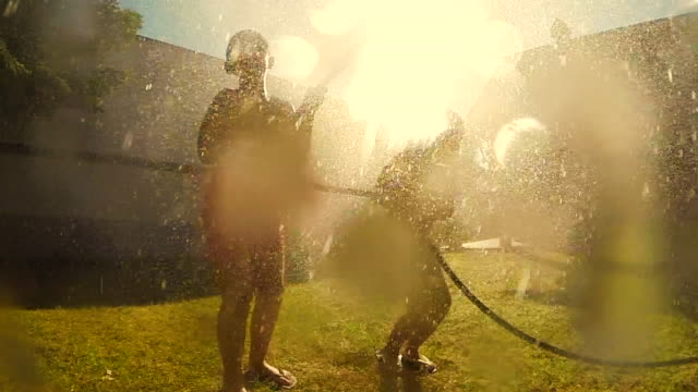 vídeos de stock e filmes b-roll de two young kids celebrating the end of school and the beginning of summer, jumping in slow motion under de hose water cooling off on the backyard home. - mangueira