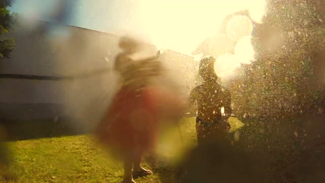 two young kids celebrating the end of school and the beginning of summer, jumping in slow motion under de hose water cooling off on the backyard home. - erfrischung stock-videos und b-roll-filmmaterial