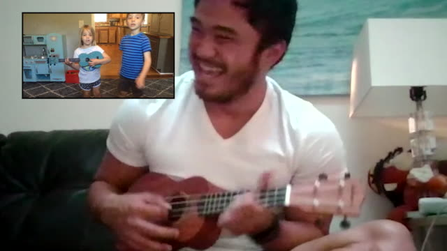 two young kids dance along with their friend playing the ukuele via video call. - the internet stock videos & royalty-free footage