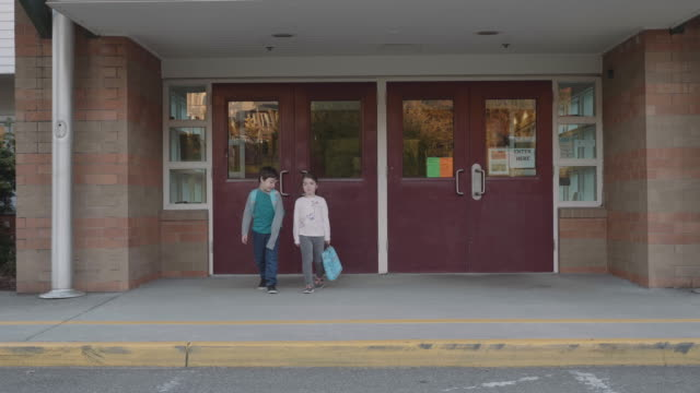 two young kids leaving school - elementary school stock videos and b-roll footage