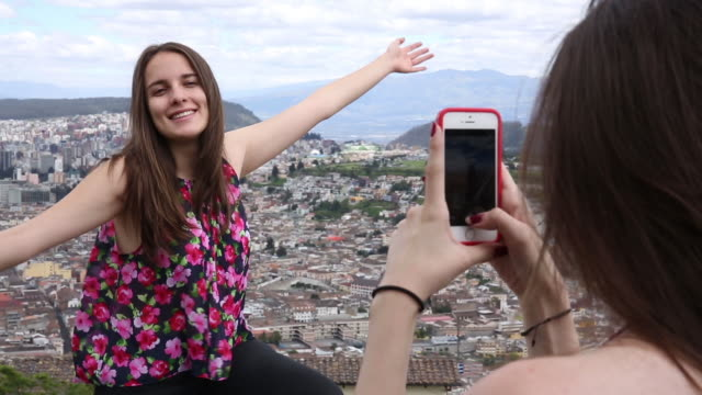Two young Latina women take selfie above city skyline