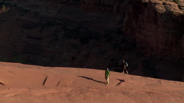 Two young male hikers walking along sandstone ridge with dark desert canyon behind them