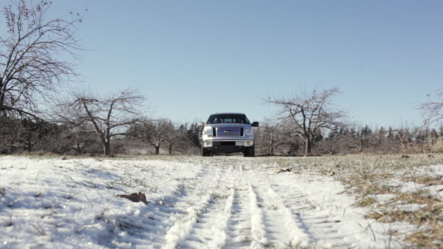 MS Two young man driving truck on snowy and rural road during day / Stillwater, Minnesota, United States