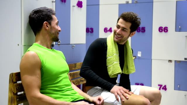 vidéos et rushes de deux jeune homme ayant une conversation dans la salle de sport, vestiaires - centre de bien être
