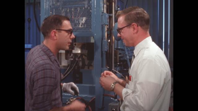 stockvideo's en b-roll-footage met two young men approving metal press project - men