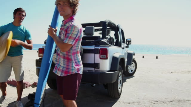 two young men arriving at beach with surfboards - 四輪駆動車点の映像素材/bロール
