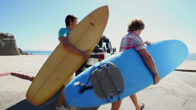 two young men arriving at beach with surfboards - 4x4 stock videos and b-roll footage