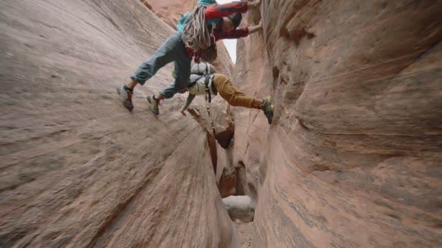 SLO MO. Two young men balance on sandstone walls above narrow slot canyon as dog looks up anxiously.