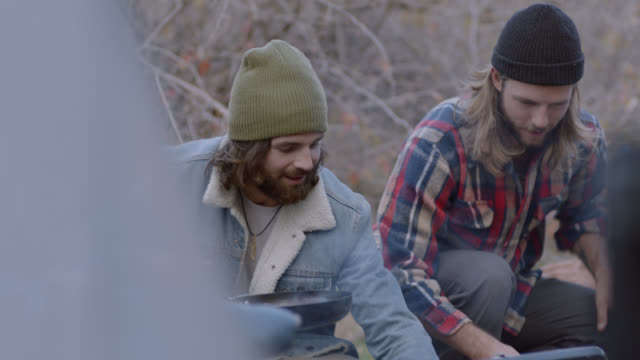 two young men cooking at camp site stand and laugh with friends. - brother stock-videos und b-roll-filmmaterial
