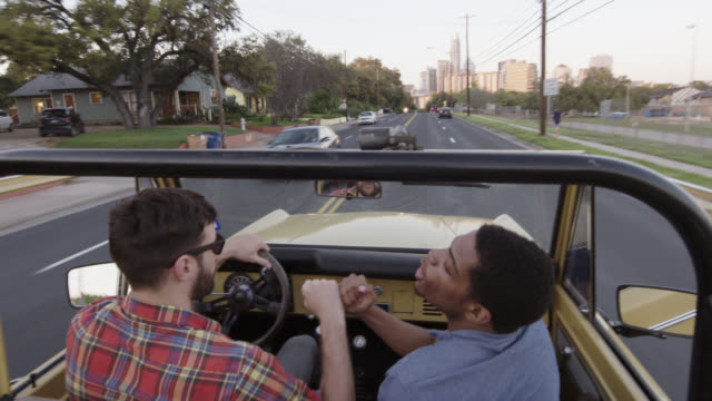Two young men fist bump in classic Ford Bronco with Austin, Texas skyline in distance