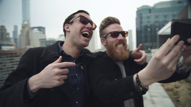 two young men goof around on chicago rooftop while taking selfies with smartphone. - eccitazione video stock e b–roll