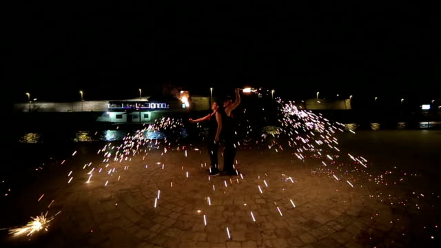 two young men have fire performance