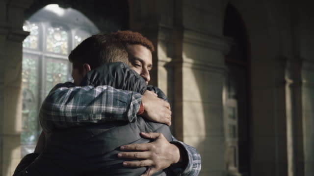 Two young men hug goodbye