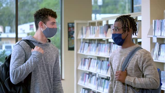 stockvideo's en b-roll-footage met twee jonge mensen in bibliotheek, universiteitsstudenten, gezichtsmaskers - 18 19 years