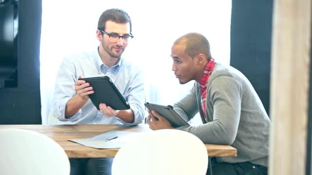 Twee jonge mannen in kantoor kijken naar digitale tabletten