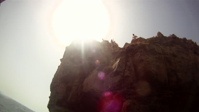 POV of two young men jumping off a cliff and doing a backflip in Malta. - Slow Motion - Model Released - HD