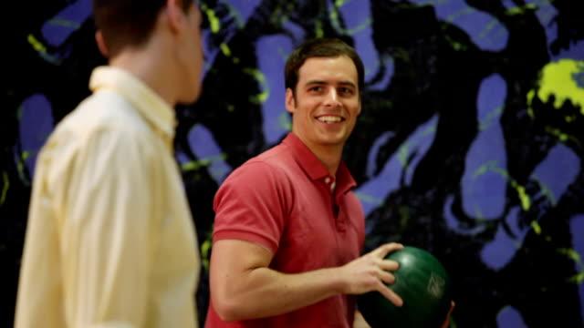 vídeos y material grabado en eventos de stock de ms selective focus two young men lining up to bowl, talking and laughing / dover, new hampshire, usa - camisa de polo