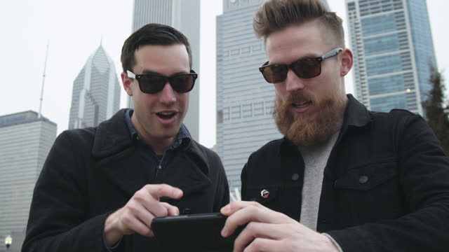 two young men look and point at smartphone and laugh with chicago skyline in background. - abspann stock-videos und b-roll-filmmaterial