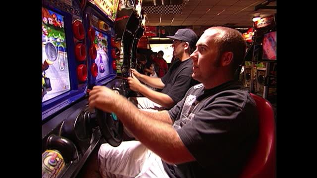 vidéos et rushes de two young men playing mario cart - style des années 2000