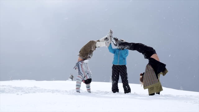 stockvideo's en b-roll-footage met two young men practice acrobatic yoga in the snow - acrobatiek