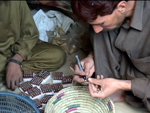 stockvideo's en b-roll-footage met two young men preparing newly produced bullets, darrah district in tribal zone at afghan border, federally administered tribal areas, pakistan, audio - vuurwapenwinkel