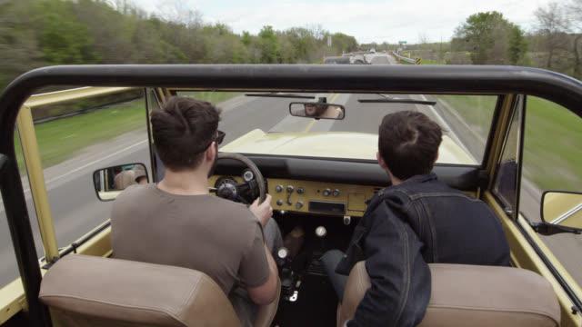 vídeos y material grabado en eventos de stock de two young men ride through country over bumpy roads in classic ford bronco - desigual con textura