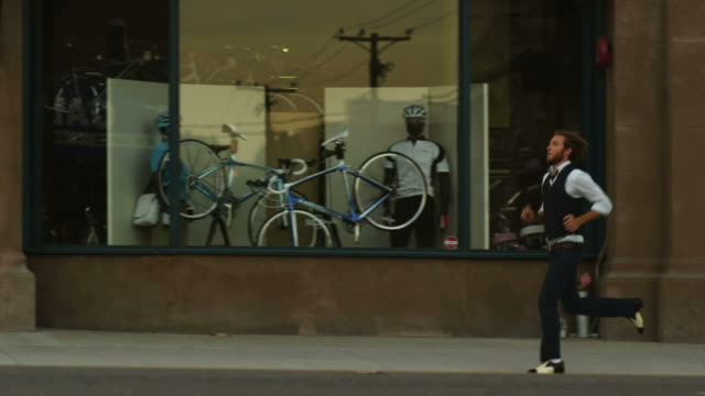 SLO MO WS TS Two young men riding bicycle on street, Salt Lake City, Utah, USA