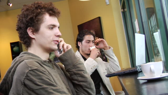 stockvideo's en b-roll-footage met ms two young men sitting in coffee shop, one using laptop, one talking on mobile phone/ vancouver, bc - zij aan zij