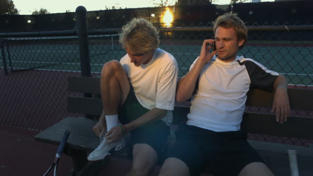 vídeos de stock, filmes e b-roll de ms, two young men sitting on bench at tennis court, one talking on mobile phone, santa barbara, california, usa - plano americano