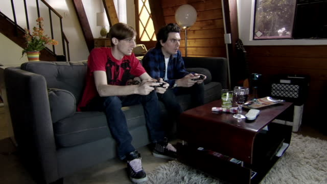 ms zi two young men sitting on sofa playing video game/ los angeles, california - young men stock videos & royalty-free footage