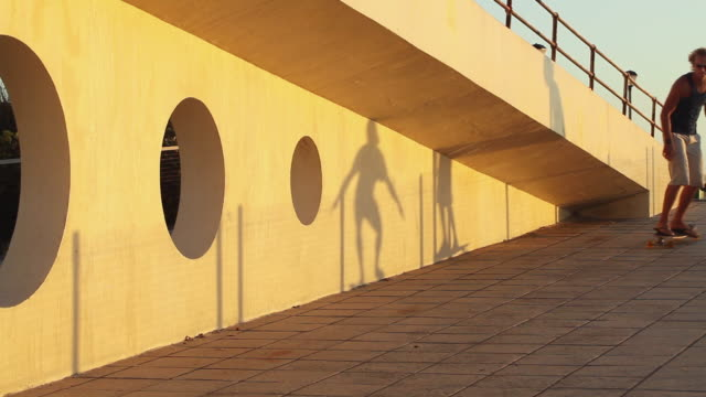 ms two young men skateboarding past beach pavilion at sunset / cape town, western cape, south africa - サーフパンツ点の映像素材/bロール