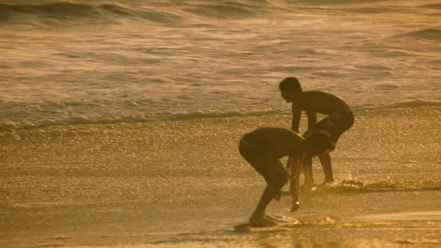 two young men skimboarding in the surf, slow motion at sunset. one falls off at the end. - skimboarding stock videos & royalty-free footage