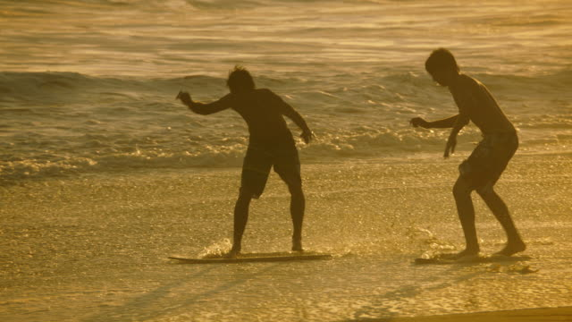 two young men skimboarding in the surf, slow motion at sunset. - skimboarding stock videos & royalty-free footage