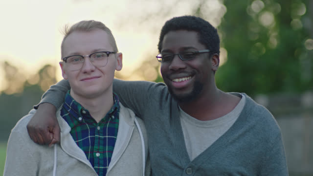 SLO MO. Two young men smile at camera with arms around each other.