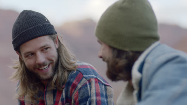 two young men talk and laugh on camping trip. - long hair stock videos & royalty-free footage