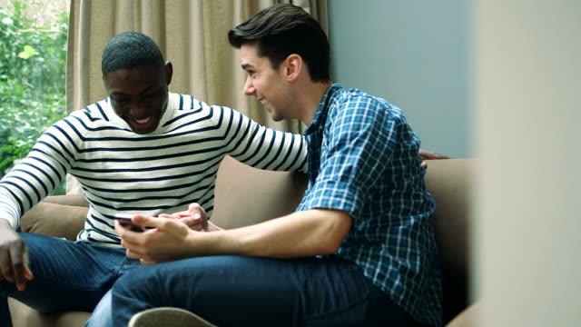 vidéos et rushes de ms tu two young men talking in living room - seulement des jeunes hommes