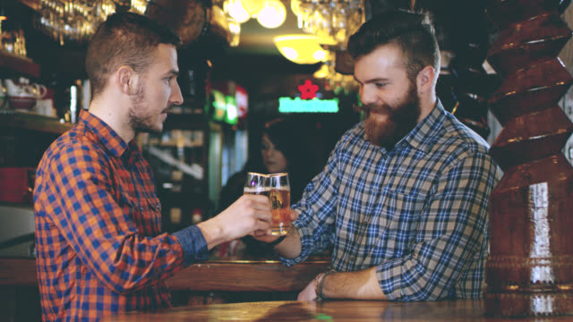 slo mo two young men toasting with beer in the pub - pilsner stock videos & royalty-free footage