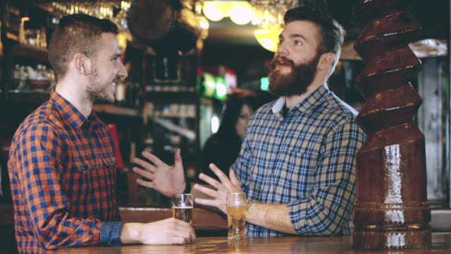 slo mo two young men toasting with beer - pilsner stock videos & royalty-free footage